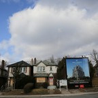 A billboard advertising a new condominium tower stands in front of dilapidated houses.