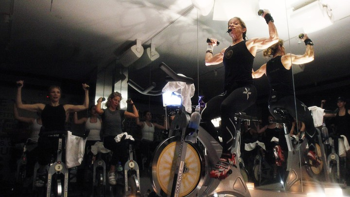 A woman lifts weights while riding a SoulCycle stationary bicycle.