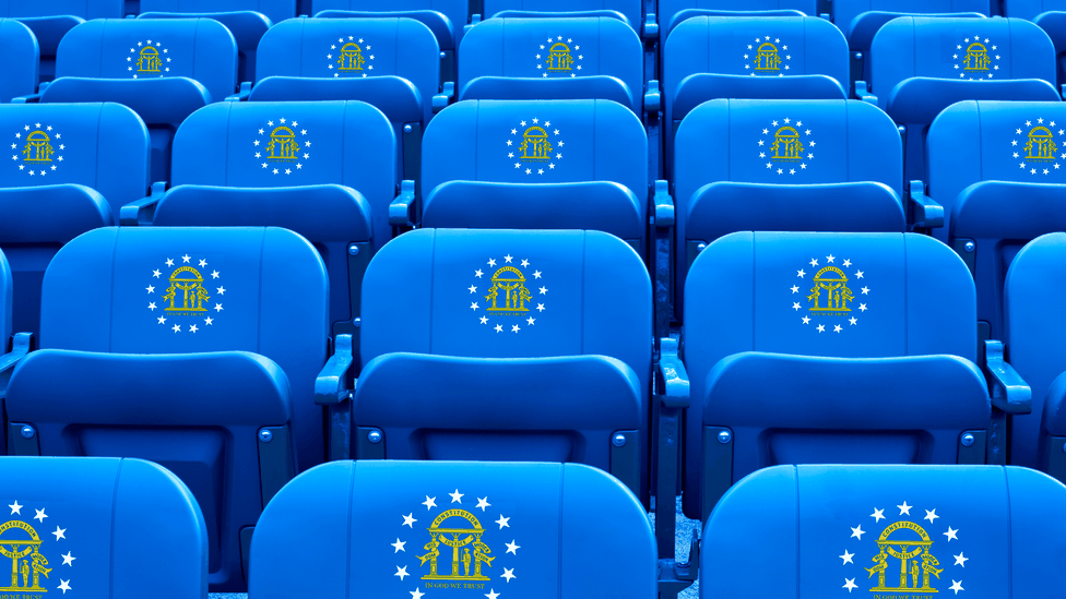 An illustration of sporting seats decorated with the Georgia state seal