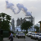 Children play on a street in front of an oil refinery