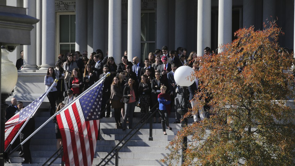 Onlookers hoping to get a view of President-elect Donald Trump stand outside the White House in Washington, D.C., on November 10.