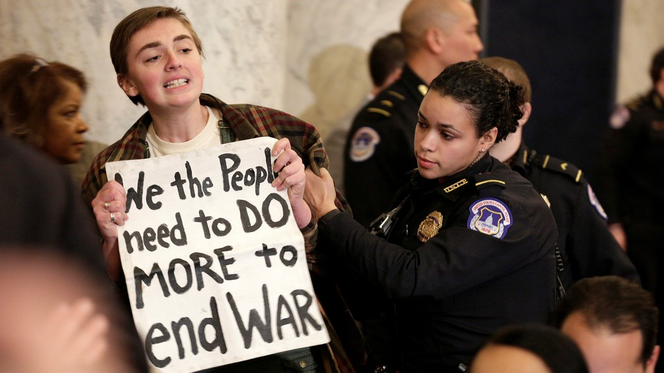 """A protester holds a sign that says """"We the people need to do more to end war."""""""