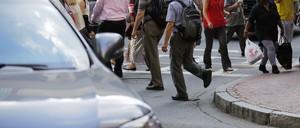 Pedestrians cross a busy street in Boston