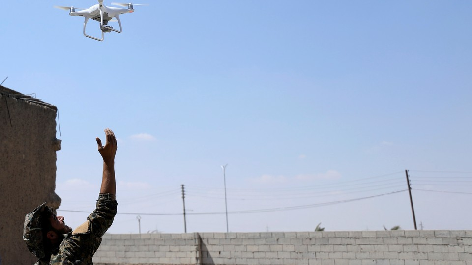 A fighter from SDF flies a drone in western Raqqa province on June 18, 2017.