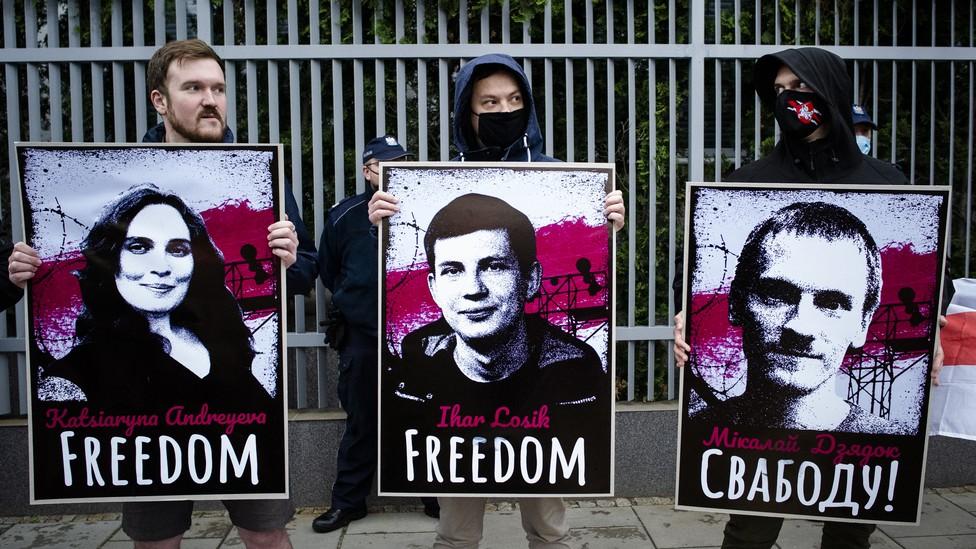 Protestors hold up images of political prisoners