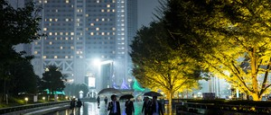 Pedestrians walk past illuminated trees, with skyscrapers in the background, on a rainy night in Tokyo.