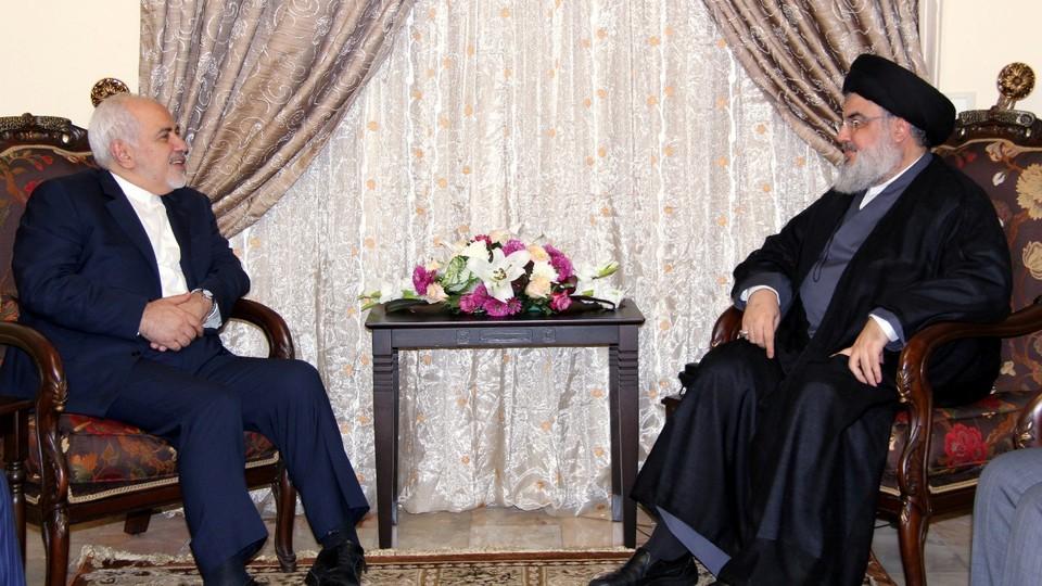 Sayyed Hassan Nasrallah and Javad Zarif sit facing each other.