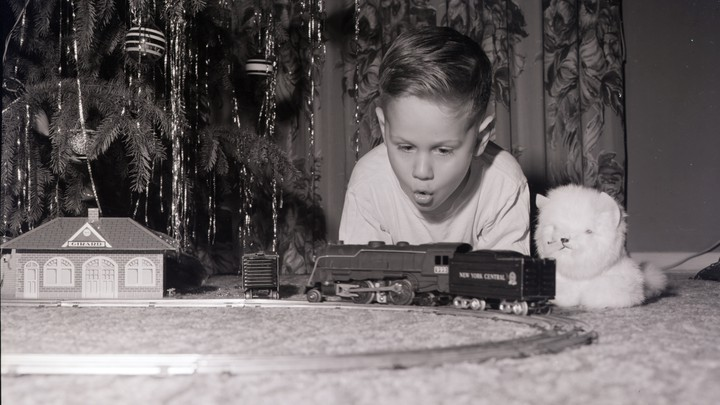 A boy looking at a toy railroad set by a Christmas tree