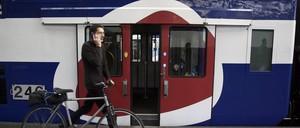 A man walks his bicycle beside a train in Paris.