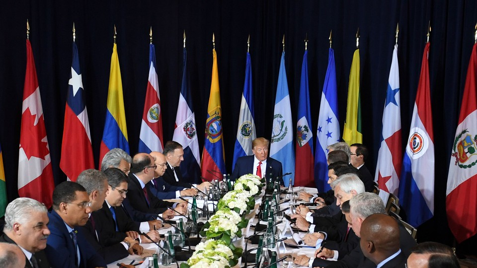 President Donald Trump sits at the head of a table surrounded by leaders from other countries and their flags.