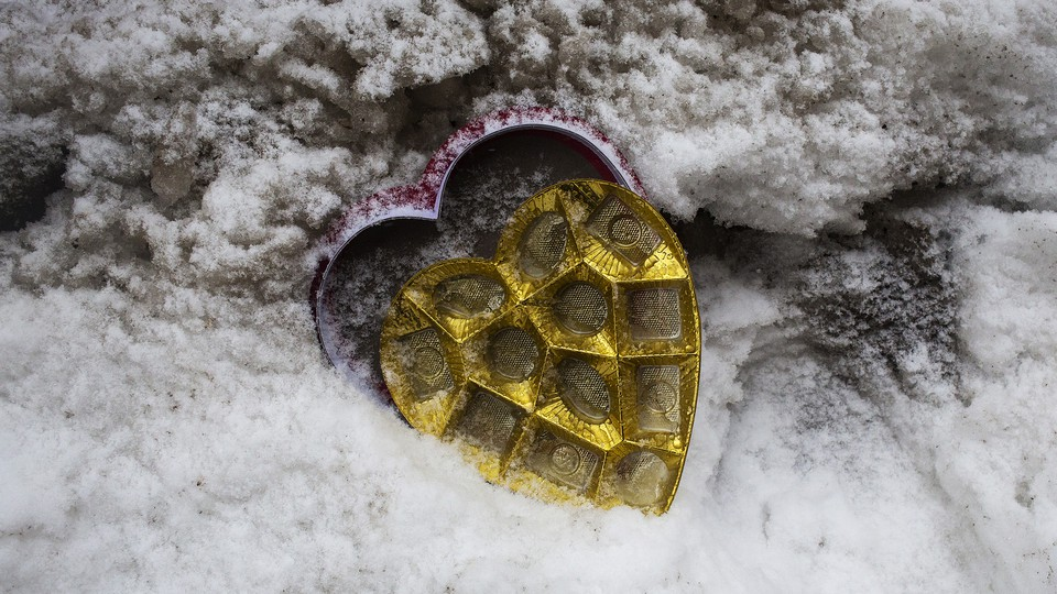 An open and empty heart-shaped box of chocolates in the snow.