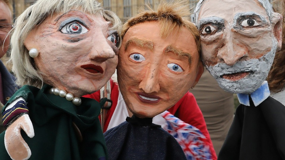 Performers pose Thursday with puppets of Prime Minister Theresa May, Tim Farron, leader of the Liberal Democrat Party, Jeremy Corbyn, leader of the Labour Party, in front of the Palace of Westminster in London.