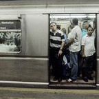 a photo of commuters in a NYC subway during the morning rush hour.