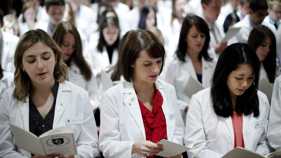 A group of students in white lab coats reads from pamphlets.