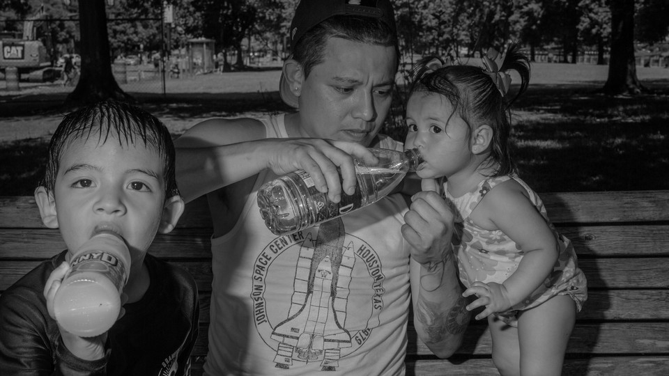 A photograph of a man holding a bottle of water to a toddler's mouth as they sit on a bench with another toddler who is drinking juice.