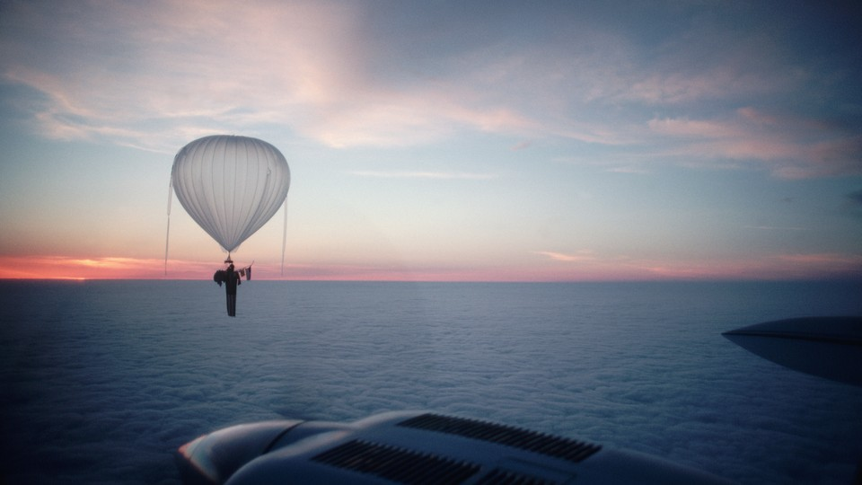 A balloon floats over a body of water with a sunset or sunrise visible in the background.