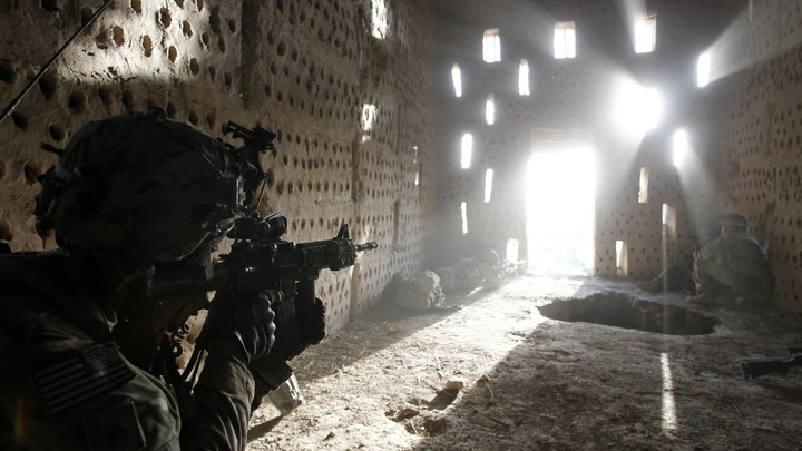 An American soldier points his rifle at a doorway after coming under fire by the Taliban while on patrol in Kandahar province in April 2012.