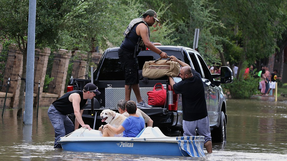Five people load up duffel bags and a dog onto a truck bed in a flooded street.