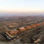 Aerial view of abandoned, unfinished homes in a barren landscape.