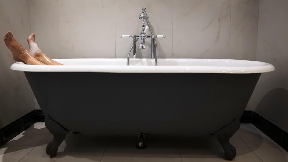 A person lying in a bathtub.