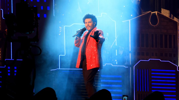 The Weeknd performing at the Super Bowl halftime show bathed in a column of light