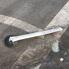 A bollard toppled over and cracked on a city street, surrounded by wheel marks