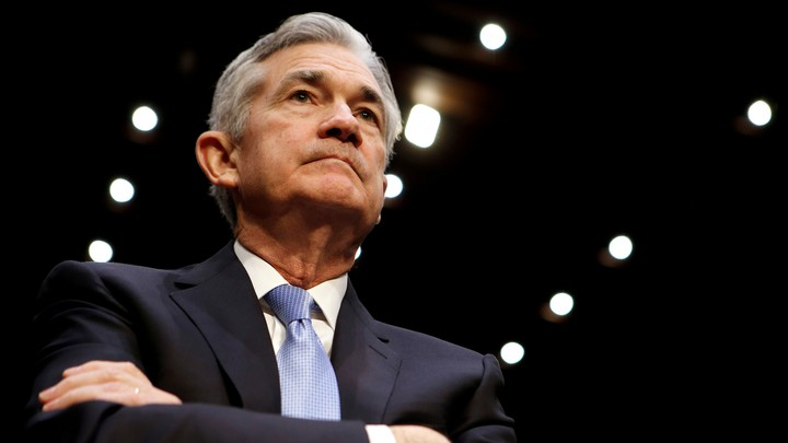 Jerome Powell looking up with arms crossed
