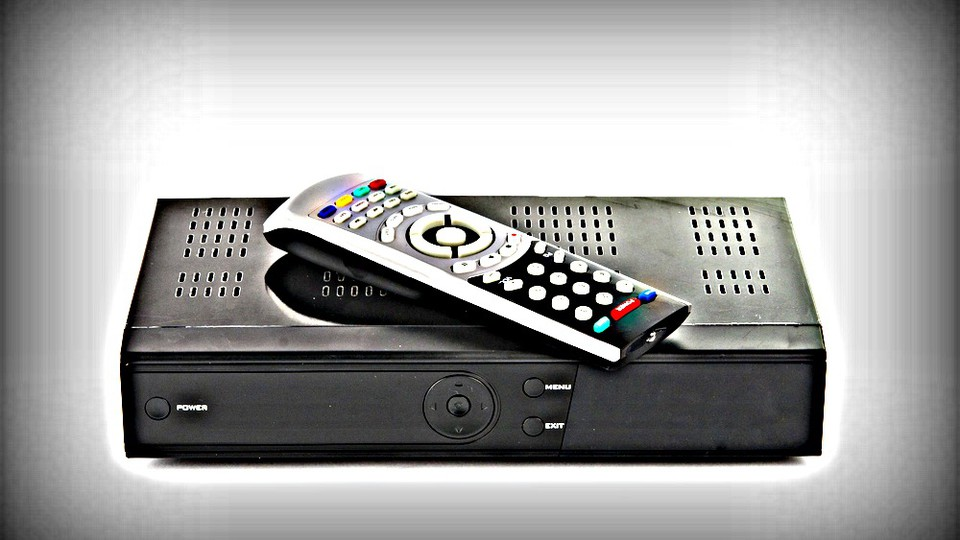A remote control on top of a cable box