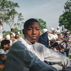 A young black man looks at the camera, sitting in a field surrounded by people wearing white.