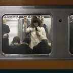 A man and woman cling to subway straps while standing on a moving subway train in Tokyo.