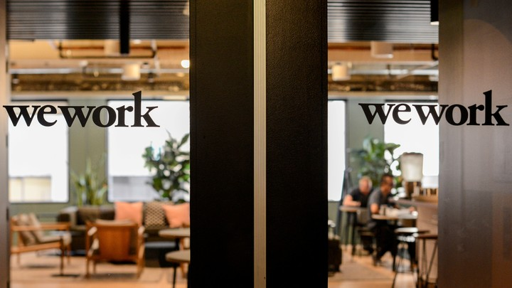 The WeWork logo is printed on a glass door, with an office visible behind it.