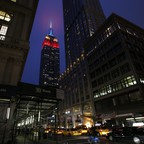 Tall buildings glow above a busy street scene in New York City