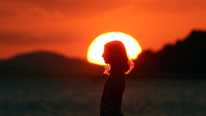 A girl stands in front of a setting sun