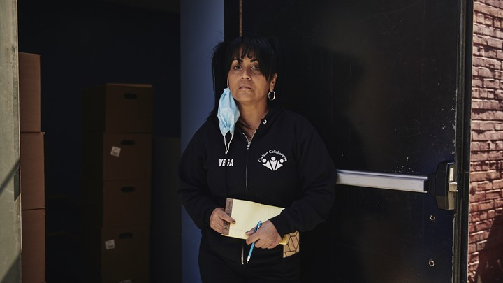A woman, dressed in a black track suit and with a blue surgical mask hanging off one ear, stands in a doorway.
