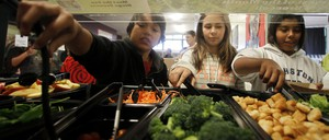 Students use tongs to fill up their plates with healthy lunch options at a school salad bar