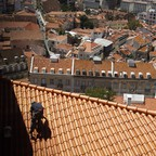 A painter works on the roof of a house above Lisbon's Mouraria neigborhood.