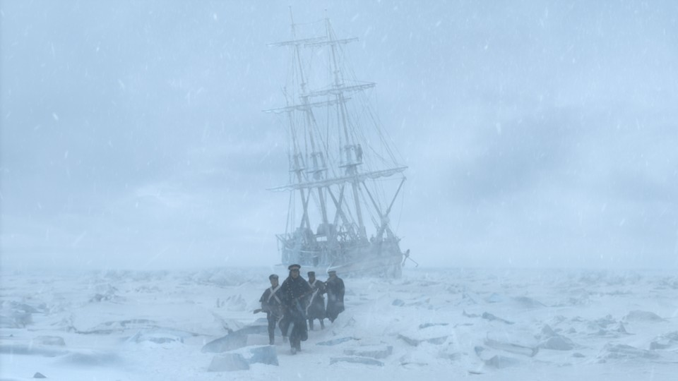 A small group of men walk across a snow-covered landscape toward the camera and away from an old ship.