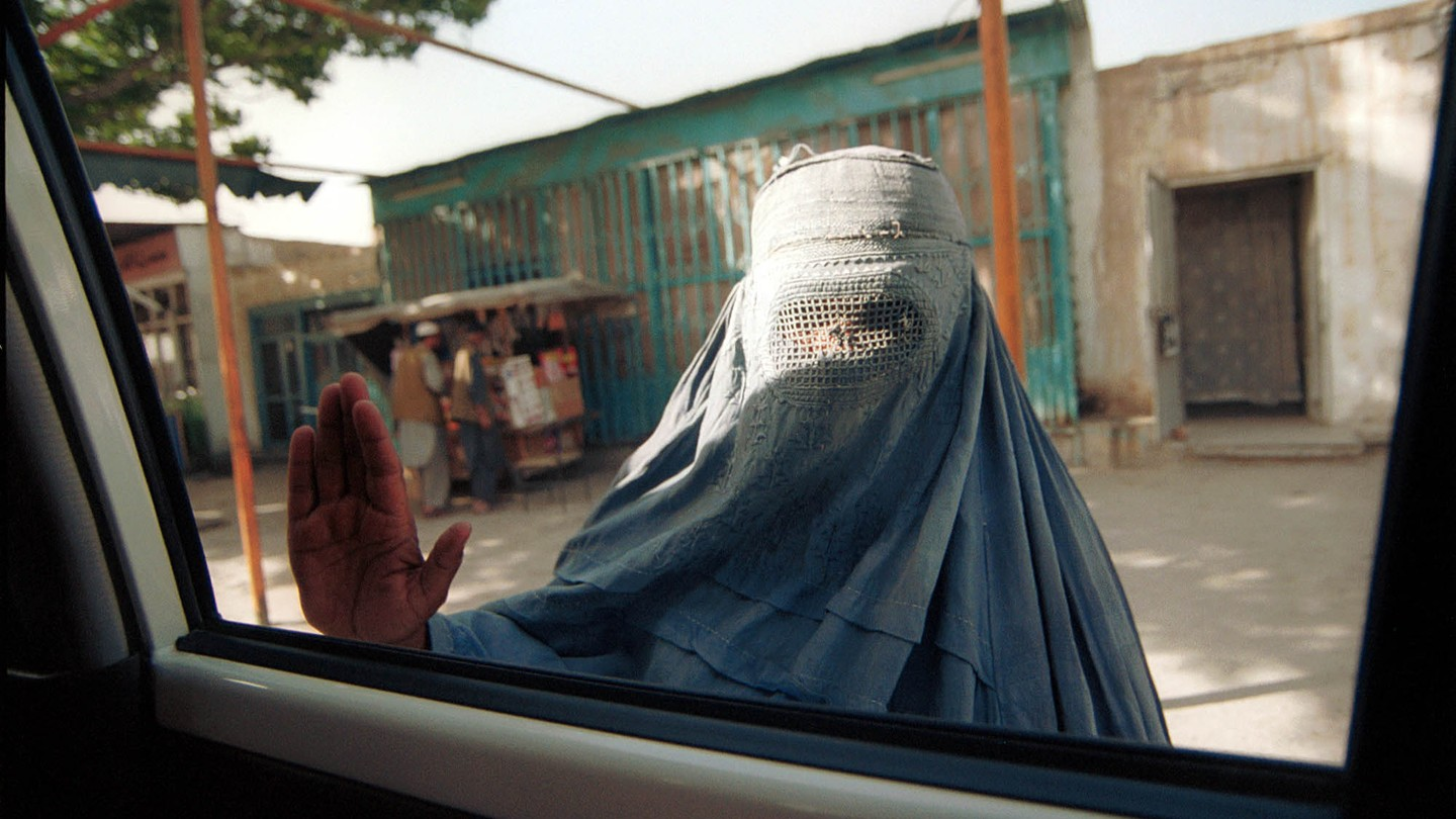 A woman in a burka puts her hand up to a car window, looking in at a passenger.