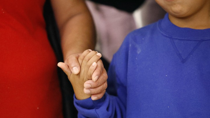 A mother and son hold hands