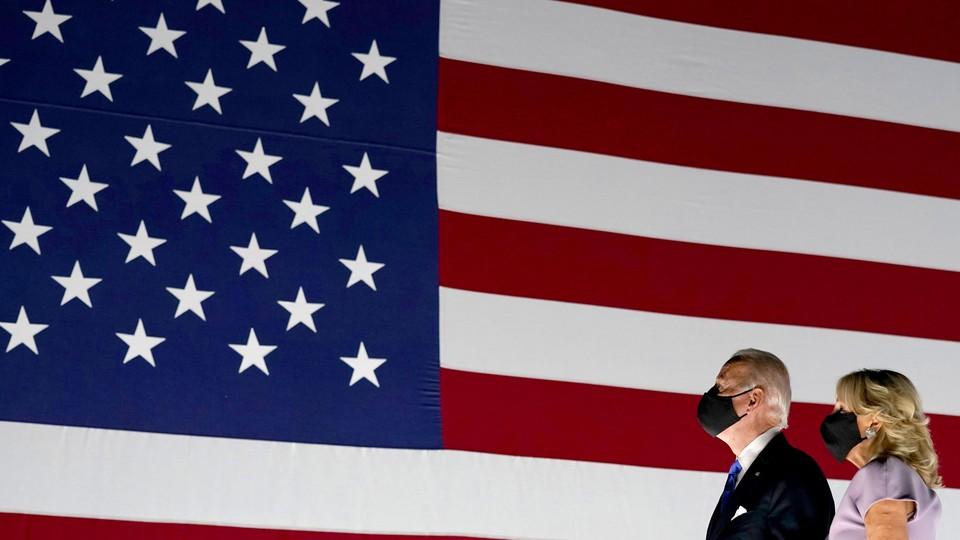 Joe and Jill Biden, masked, look at the American flag.
