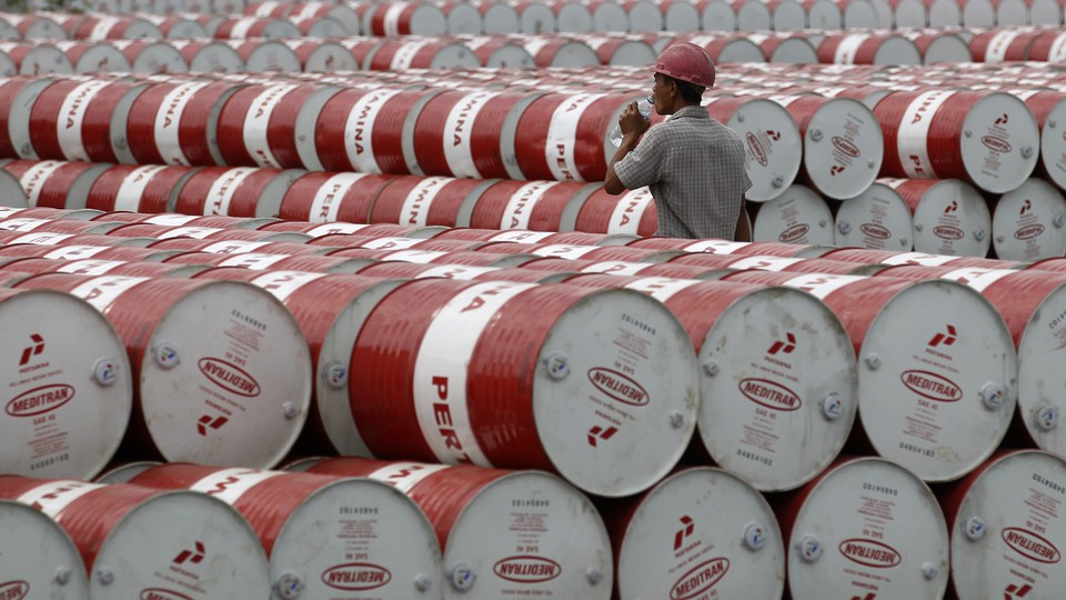A worker walks between stacks of red and white oil barrels.