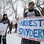 """Protesters with signs reading """"Arrest Synder"""" and """"Fix Flint Now."""""""