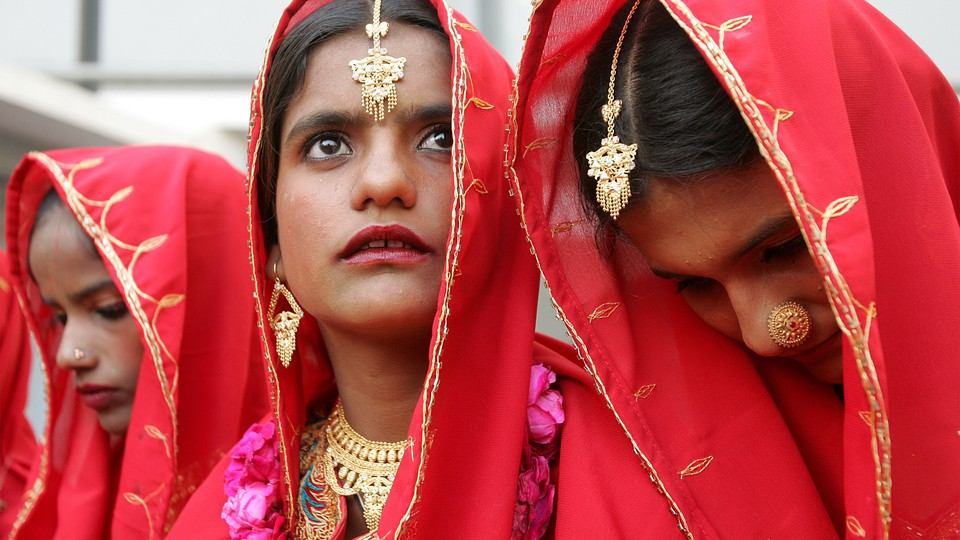 A young Pakistani bride in a sari looks up at the sky during a mass wedding ceremony in Karachi.