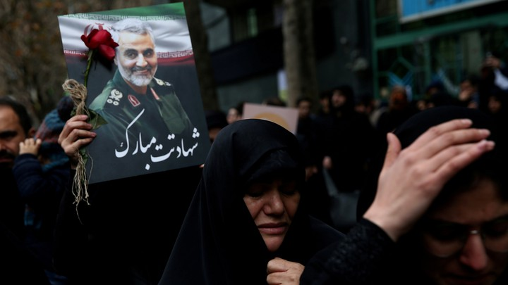 A protester in the middle of a crowd in Iran holds a rose and a photograph of Qassem Soleimani.