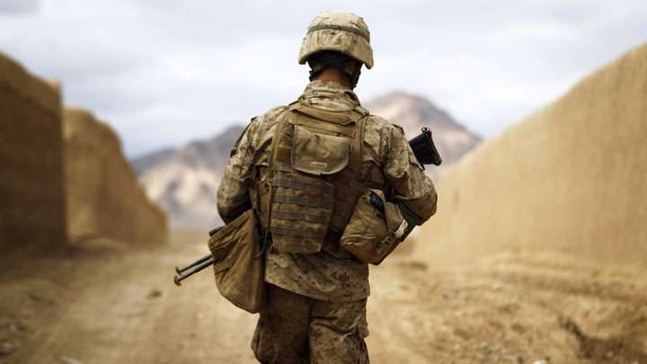 A U.S. Marine with his back to the camera walks through the town of Nabuk in southern Afghanistan.