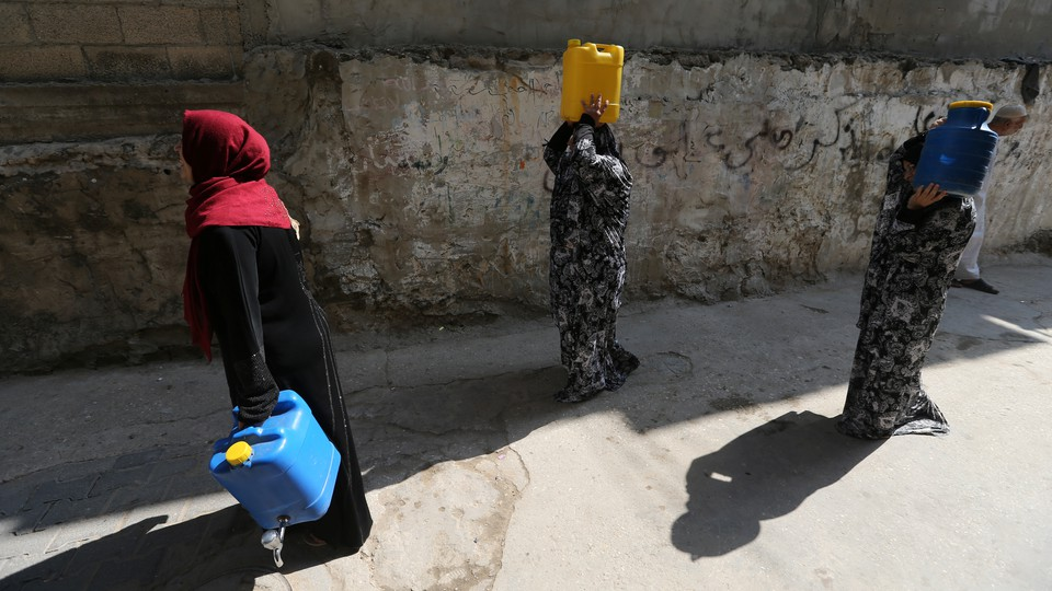 Palestinian women walk after fetching potable water in the Al-Shati refugee camp (also known as Beach Camp) in Gaza City, September 10, 2019.