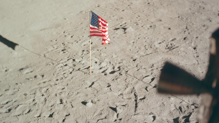 The American flag stands upright on the surface of the moon.