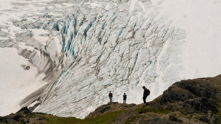 Hikers stand on a cliff overlooking Exit Glacier, in Alaska's Kenai Fjords National Park