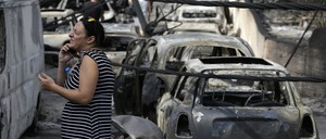 A woman stands amid the charred remains of burned-out cars in Mati, east of Athens.