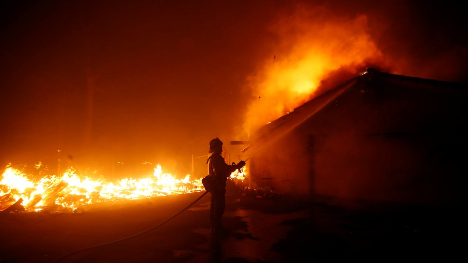 A firefighter battles the Woolsey Fire in Malibu